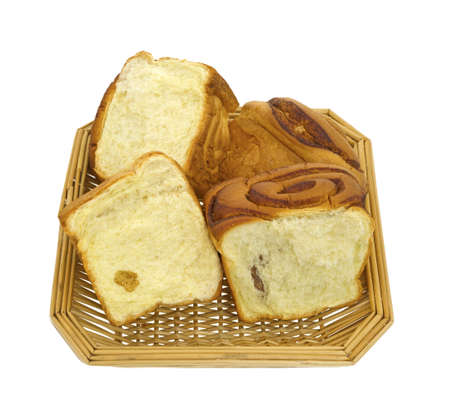 Several sections of freshly made cinnamon bread in a wicker basket on a white background