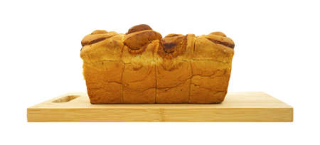 Side view of a freshly made loaf of cinnamon bread on a wood cutting board