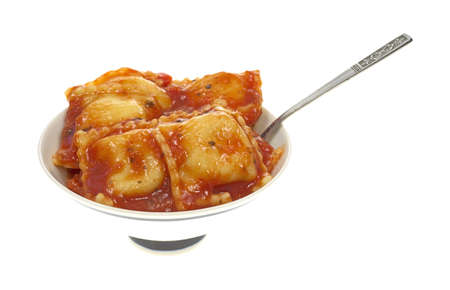 A small dish with a single serving of ravioli filled with cheese on a white background