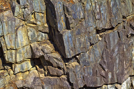 fissures: A colorful rock face with cracks and fissures in the early morning light  Stock Photo