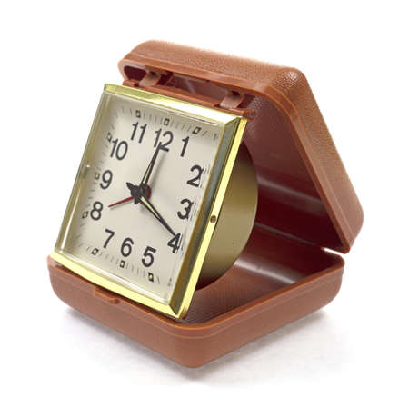 An old traveling alarm clock on a white background  photo