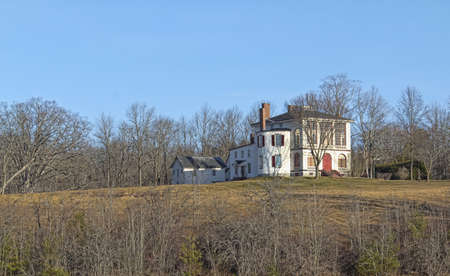 Distant view of an old abandoned house amongst trees with blue sky  photo