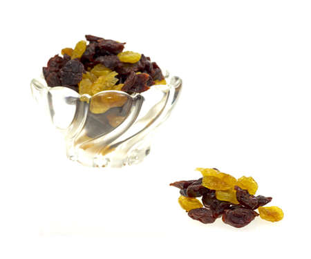 A bowl filled with golden and red dried sweet cherries in the background with a small group of cherries in the foreground