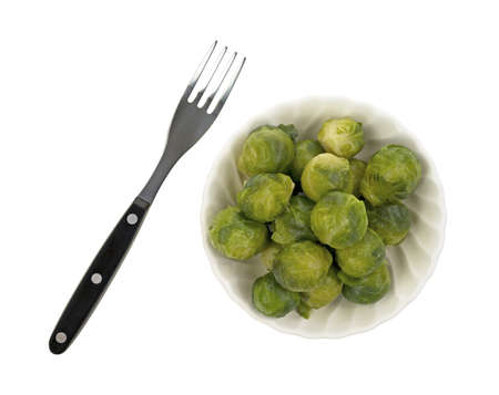A small bowl filled with Brussels sprouts and a fork on a white background Stock Photo - 13506293