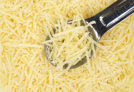 Close view of shredded Parmesan cheese with a small measuring spoon Stock Photo - 13642434