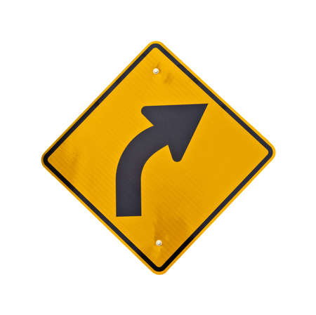 A bright yellow hazard sign of road curved ahead on a white background   photo