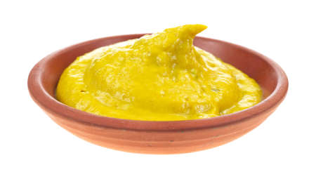 Yellow jalapeno mustard in a small clay dish on a white background