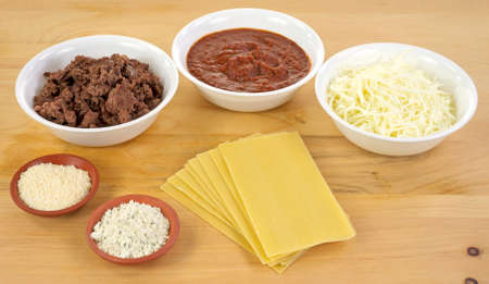 All of the ingredients for home made lasagna with browned beef, thick herb sauce, mozzarella cheese, Parmesan and Romano cheese and pasta on a wood cutting board Stock Photo - 14062470