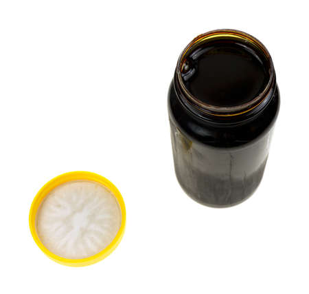molasses: An opened jar of molasses with cover separate on a white background