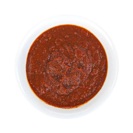 Top view of a bowl of thick tomato herb sauce on a white background