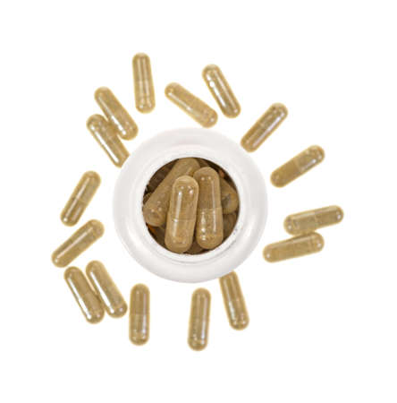 A white plastic bottle filled with green tea extract capsules and several scattered capsules around the base  photo