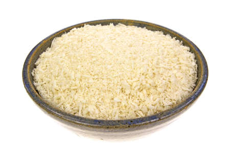 An old bowl filled with flaked panko style bread crumbs on a white background
