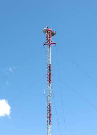 The top of a cellular telecommunications tower with blue sky and clouds in the background  photo