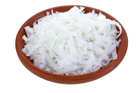 A small clay bowl filled with shredded coconut on a white background