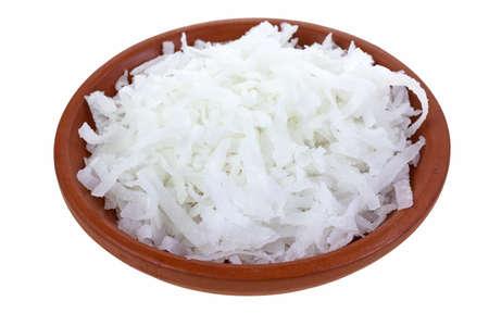 Een kleine klei kom gevuld met geraspte kokos op een witte achtergrond