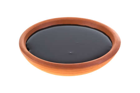 A small dish with molasses on a white background