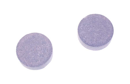 Two grape flavored antacid tablets on a white background
