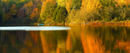 Idyllic fall foliage scene with reflections on lake with a wisp of wind ripples  photo