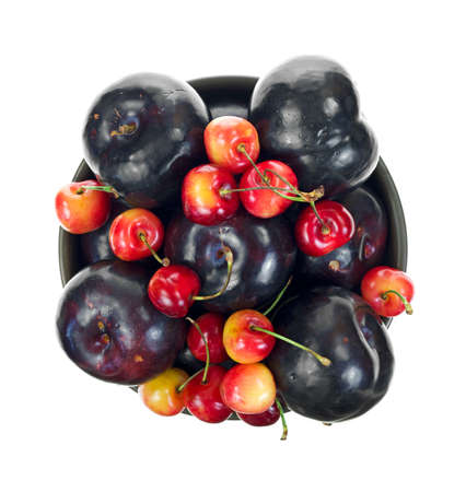 Top view of a bowl filled with ripe red cherries and plums on a white background Stock Photo - 14658746