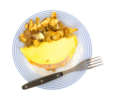 Top view of a small omelet with roasted potatoes on a blue striped plate with fork on a white background  photo