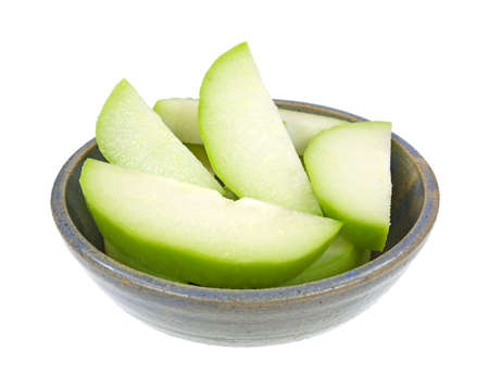 chayote: Several slices of fresh chayote squash in on old stoneware bowl on a white background  Stock Photo