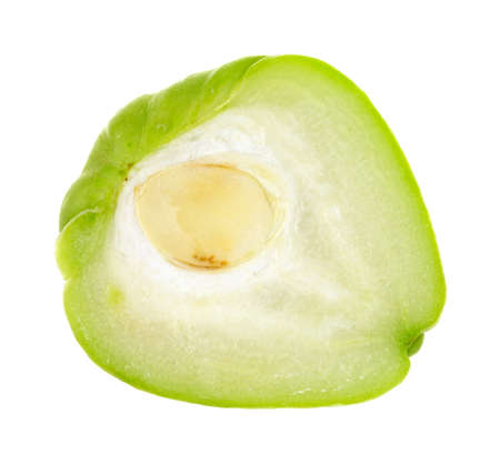 chayote: Close view of a chayote squash cut in half on a white background.
