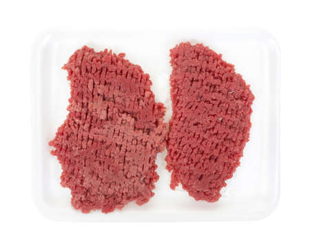 Two small raw beef cubed steaks on a white foam meat tray