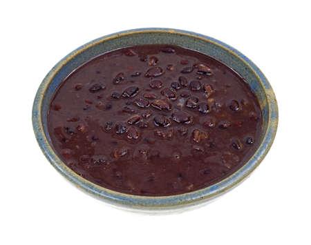 Een portie van zwarte bonen soep in een oude kom op een witte achtergrond