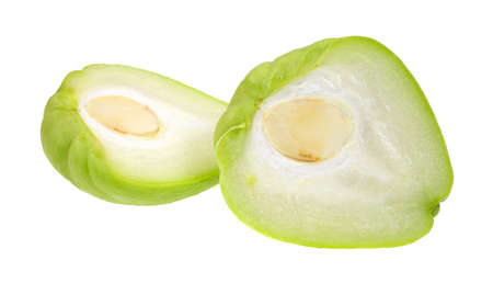 A chayote squash that has been cut in half on a white background