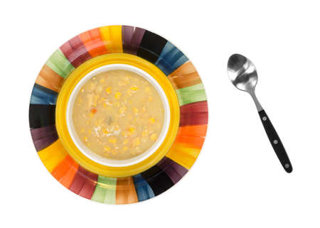 Top view of a bowl of old fashioned thick and creamy corn chowder in bowl on a colorful dish with a soup spoon to the side on a white background  photo