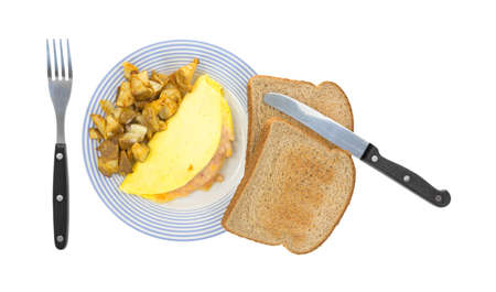 A small yellow omelet with potatoes and whole wheat toast on a plate with silverware  photo