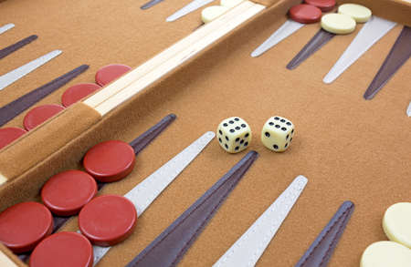 Two dice with several pieces at angle of backgammon game.