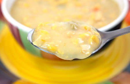 A spoonful of corn chowder in the foreground with the remainder of the meal in a bowl on a dish in the background  Imagens