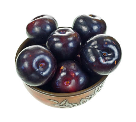 An old metal bowl filled with ripe plums on a white background  Stock Photo - 15140349