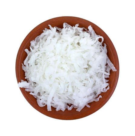 白い背景に細かく刻んだココナツでいっぱい小さな粘土ボウルのトップ ビュー