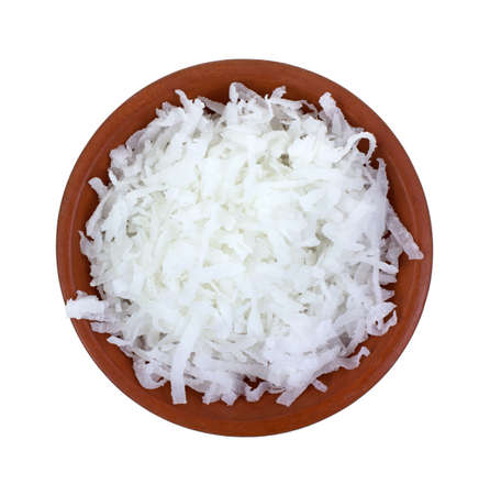 flake: Top view of a small clay bowl filled with shredded coconut on a white background  Stock Photo