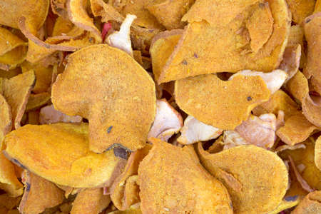 A very close view of sweet potato chips with small pieces of dehydrated apple slices.