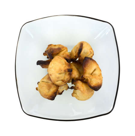 burned out: Top view of a bowl with several crab rangoon appetizers that have been cooked to long on a white background