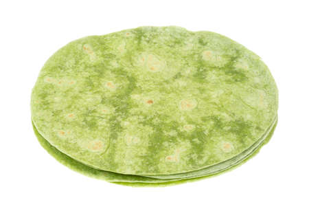 A small stack of round green spinach wraps on a white background  Imagens