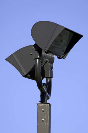 Two large halogen outdoor lighting on a square metal post