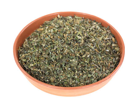 catnip: A small bowl filled with catnip herbs on a white background  Stock Photo