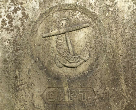 chiseled: A chiseled  anchor and chain above a captains engraving on a very old tombstone