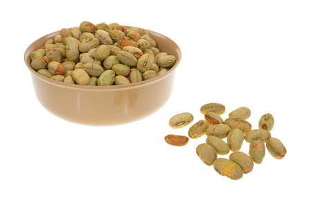 A small bowl filled with edamame soybeans with several separate in the foreground on a white background  photo