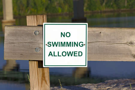 no swimming: A bright No Swimming Allowed sign on a wood fence with distant water in the background
