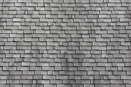 Rows of asphalt shingles that have been worn and stained by the elements