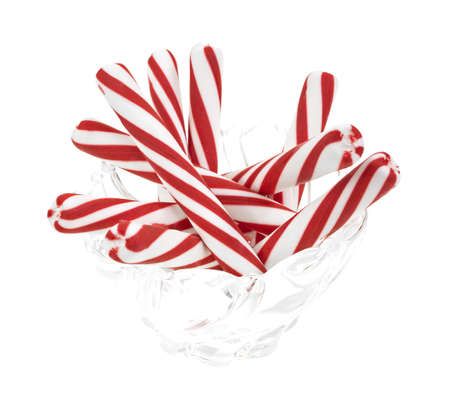 A group of peppermint candy sticks in a glass bowl on a white background. photo