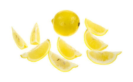 A whole lemon in the background with several wedges in the foreground on a white background