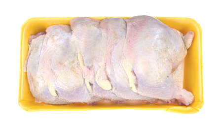 Top view of a large yellow meat tray filled with fresh chicken legs and thighs on a white background  photo