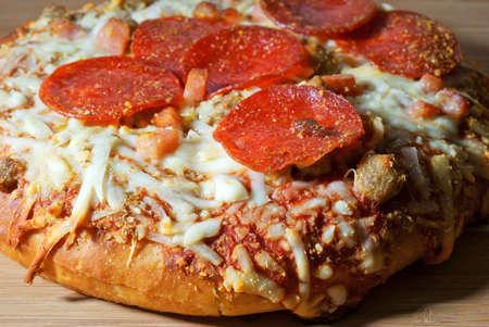 Een zeer dichte mening van een persoonlijke formaat dikke korst pizza met worst pepperoni en ham op een houten snijplank