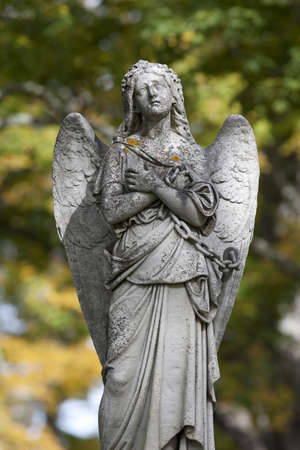 angel cemetery: A sad angel with wings and arms folded against her chest looking upwards with a chain in hand  Stock Photo